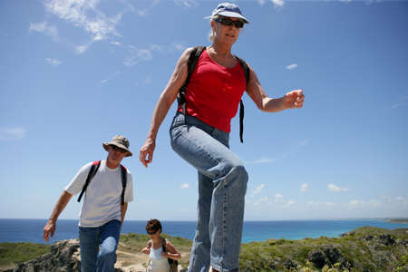 Group of senior persons hiking by a sunny day photo