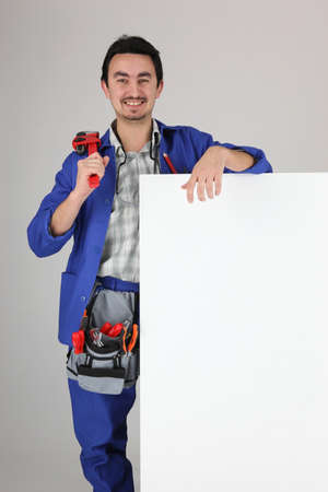 Man with blank board and toolbelt photo