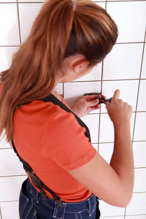 woman using a screwdriver for putting an outlet photo