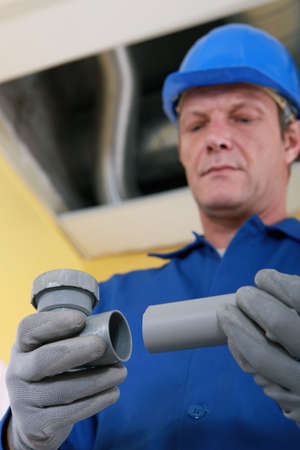 qualified worker: Plumber fixing replacement pipe Stock Photo