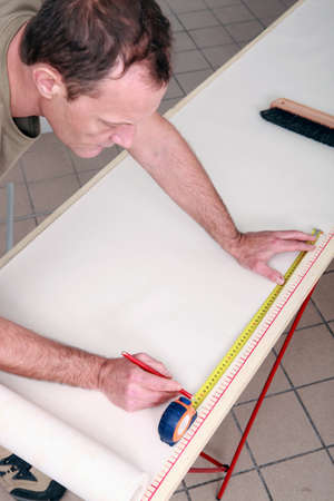 Man measuring wall-paper photo