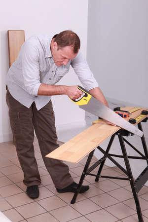 handsaw: Carpenter using a handsaw