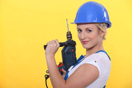 jumpsuite: blonde woman holding a power drill