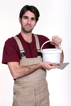 grout: Man with a pot of grout Stock Photo