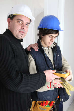 tradespeople: Workers using a multimeter