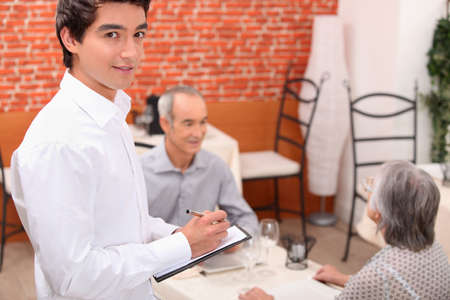 approaching: Young waiter approaching an older couple to take their order in a restaurant