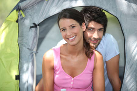 camping pitch: Couple sat by entrance to tent Stock Photo