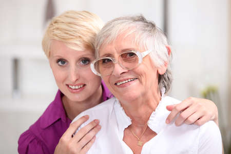 Woman posing with her elderly mother photo