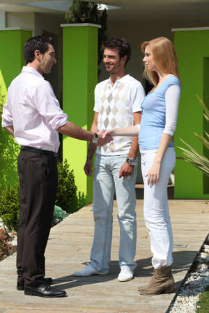 deal making: Couple shaking estate-agents hand