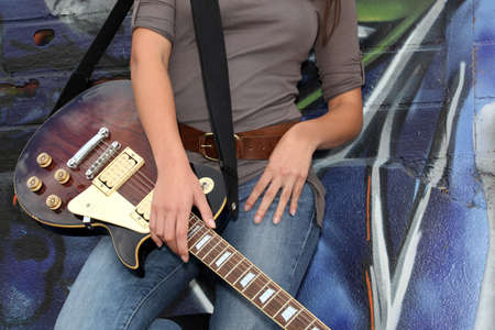 Woman beat guitar: Guitar on womans legs