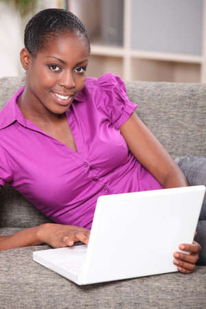 ebony: black woman doing computer and relaxing on a sofa