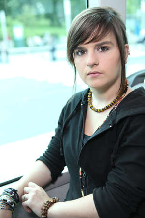 make public: Funky young woman sitting on a tram