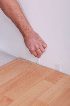 Man using plastic wedges whilst laying parquet photo