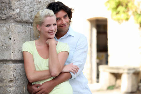learnt: Couple leaning against stone wall Stock Photo