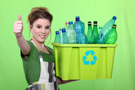 selecting: woman recycling plastic bottles