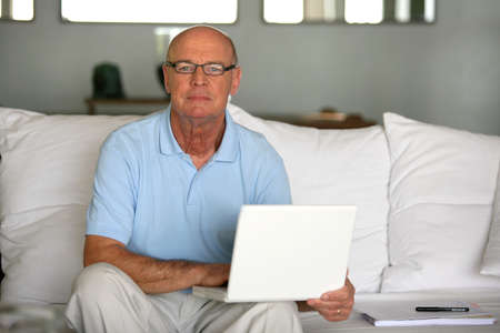 practical: Bald man using laptop at home