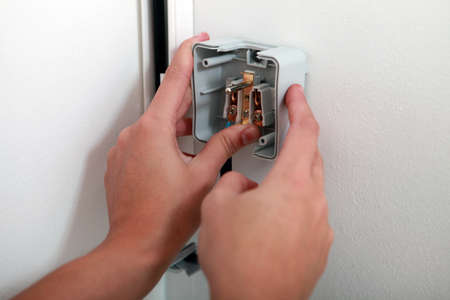 attaching: electrician attaching electrical outlet to wall Stock Photo
