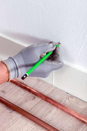 Plumber marking x on wall photo