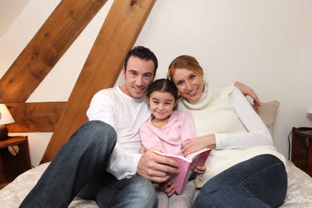 Parents and daughter reading together photo