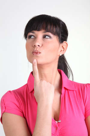 a woman putting her finger on her chin photo