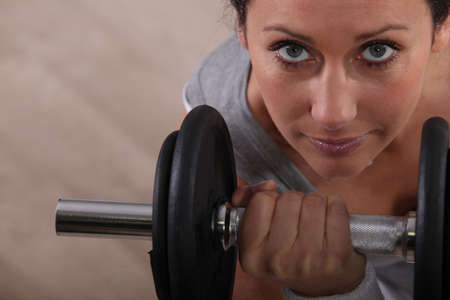 young woman doing dumbbell exercises photo