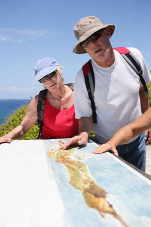 Hikers looking at a map by the coast photo