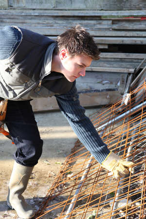 Construction worker lifting rusty wire mesh photo