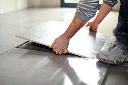 lain: Man laying floor tiles Stock Photo