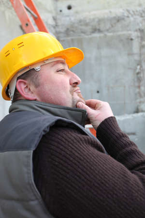 incertitude: Worker stroking his chin