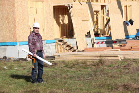 Foreman stood by unfinished wooden house photo