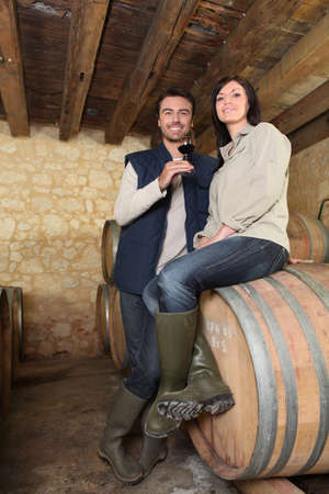 a couple of wine producers in a cellar photo