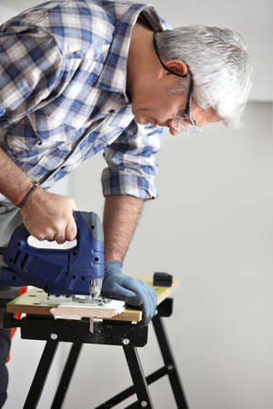 Gray-haired handyman using an electric drill photo