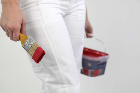 paintbucket: Decorator with red paint and brush