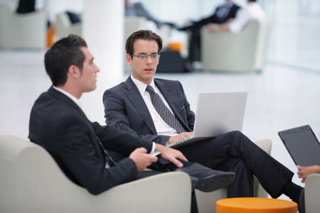 Businessmen sat in a waiting area photo
