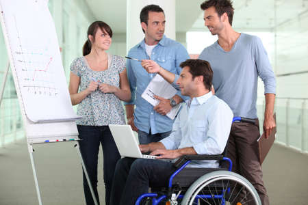 Man in a wheelchair working in an office Stock Photo