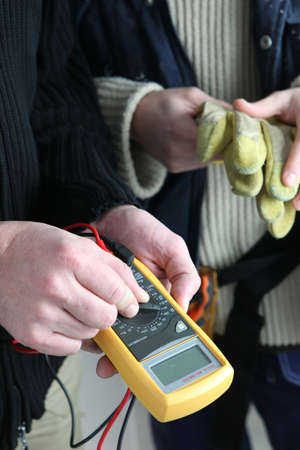 contador electrico: Dos electricistas con voltímetro