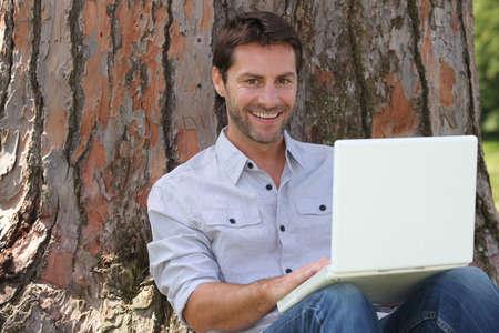 shirtsleeves: Smiling man using laptop