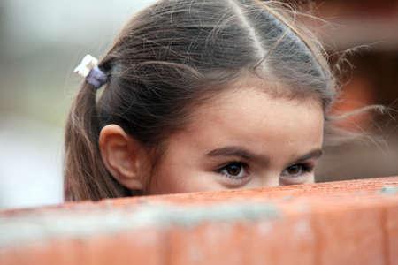 leer: Girl peeking over a brick wall
