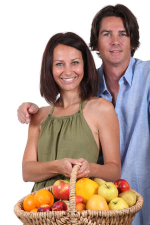 Man and woman with a basket of fruit photo