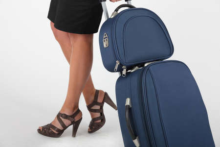 Closeup of a woman wheeling carry-on luggage photo