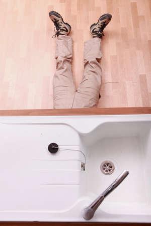 sink drain: Man under sink