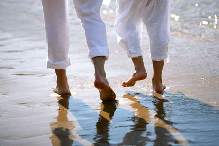 footprints in the sand: Couple walking barefoot by the sea