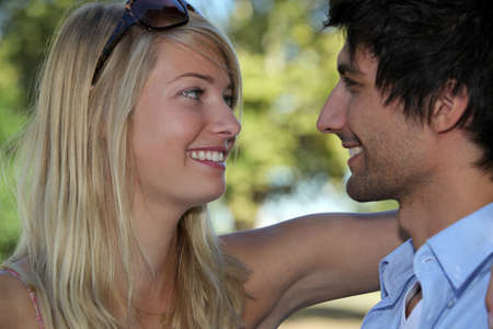gazing: Young couple in love embracing in the sunshine Stock Photo