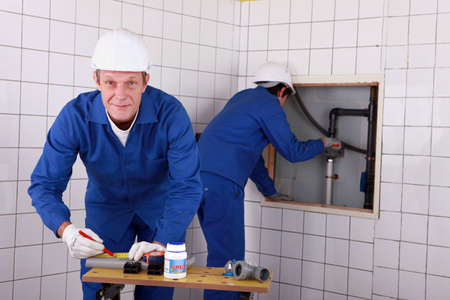 Laborers working on piping Stock Photo