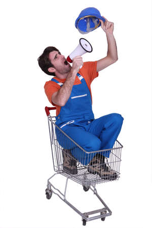 publicize: Construction worker in a trolley with a megaphone Stock Photo