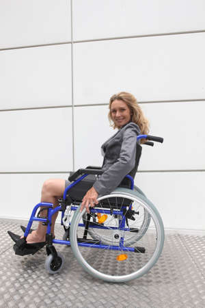 wheelchair access: Smiling businesswoman in a wheelchair on a ramp