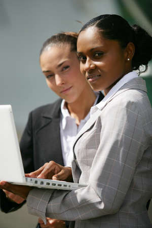 facing the camera: Two young women with laptop facing camera Stock Photo