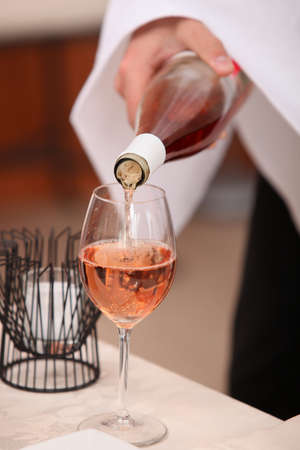 Waiters hand pouring a bottle of rose wine photo