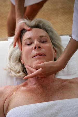 mujeres mayores: Mujer mayor que recibe masaje en la cabeza