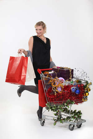 Woman standing by trolley full of Christmas gifts photo